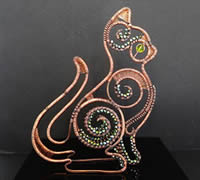 A cat made of copper wire on a black background.